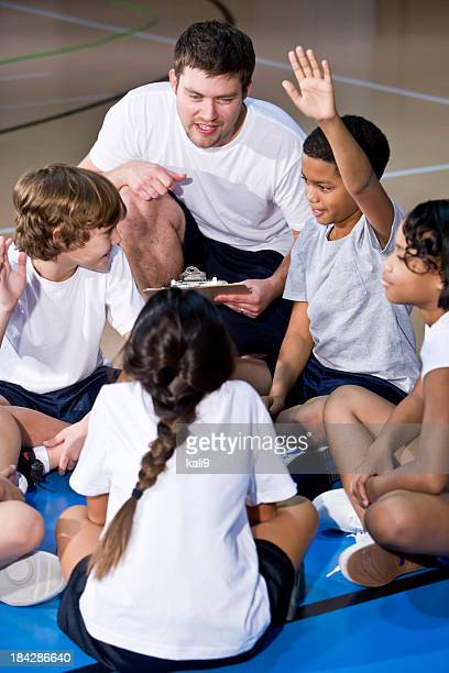 Diverse group of children in gym huddled with coach