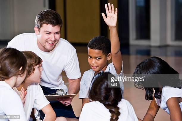Diverses groupe d'enfants en salle de gym avec entraîneur
