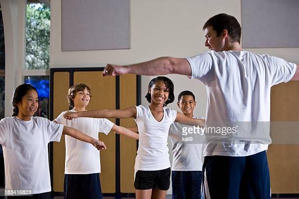 Divers groupe d'enfants dans la salle de sport avec professeur de l'Éducation physique