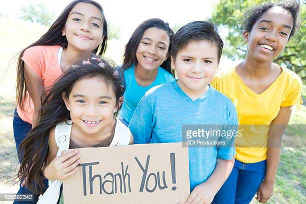 Diverse group of children with 'Thank You' sign