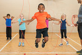 Smiling boy is skipping rope.  The boy in the foreground is shown while jumping in the air, and there are three other children with ropes in the background.  There is an adult on the right side of the