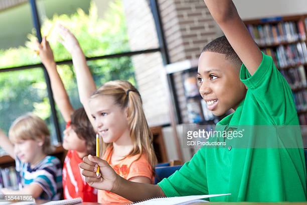 Diverse group of elementary students raising hand in class