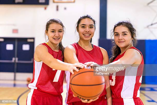 Diverse group of female basketball players holding a basketball