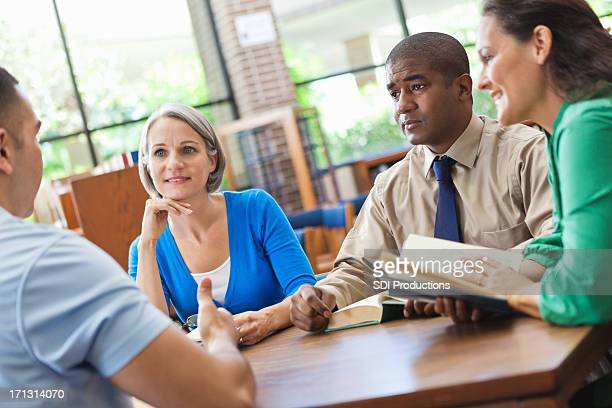 Diverse group of friends discussing book in library