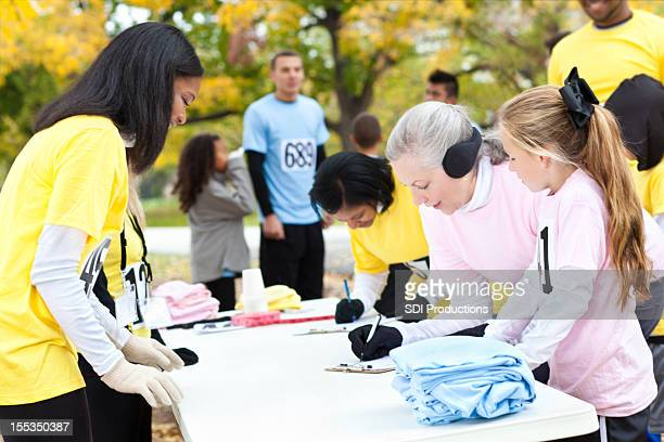 Diverse group of people signing up at charity run/walk event