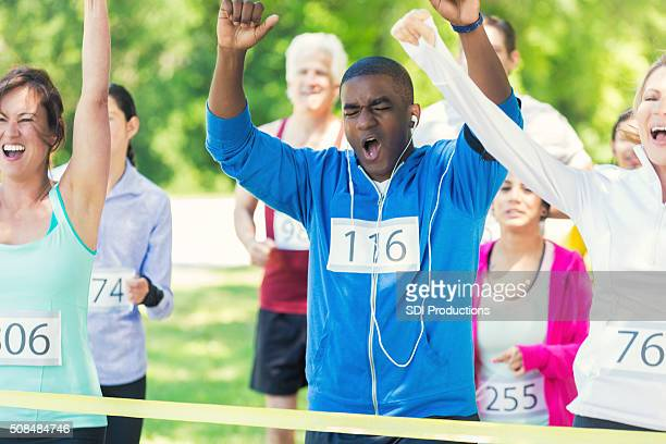 Diverse group of runners celebrate at finish line