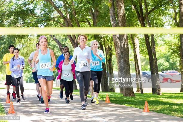 Diverse group of runners racing toward marathon finish line