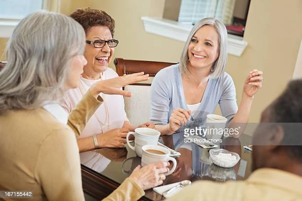Gruppo eterogeneo di senior amici avere caffè insieme a casa