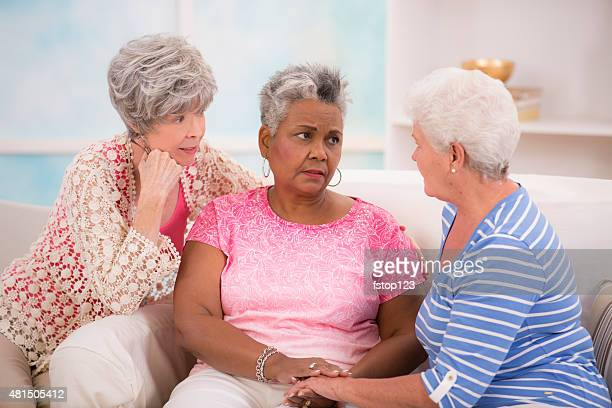 Groupe diversifié des femmes seniors console un (e) ami (e). Maison.