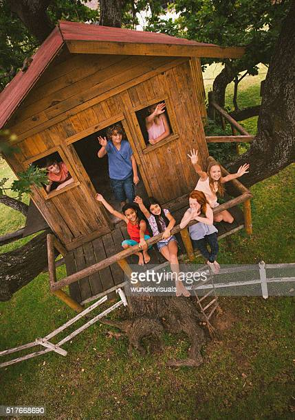 Diverse group of smiling children in a wooden treehouse waving