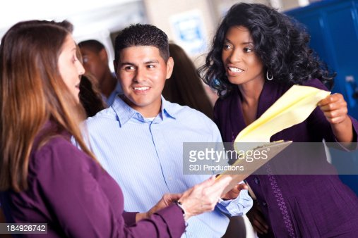Stock Photo : Diverse group of teachers in discussion at school locker ...