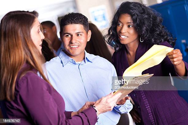 Diverse group of teachers in discussion at school locker area