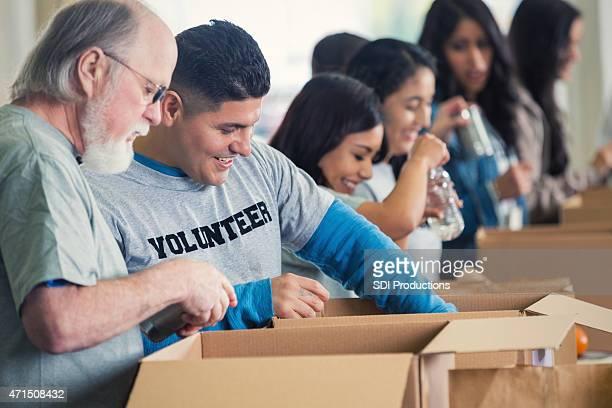 Diverso grupo de voluntarios clasificación donado comestibles en banco de alimentos