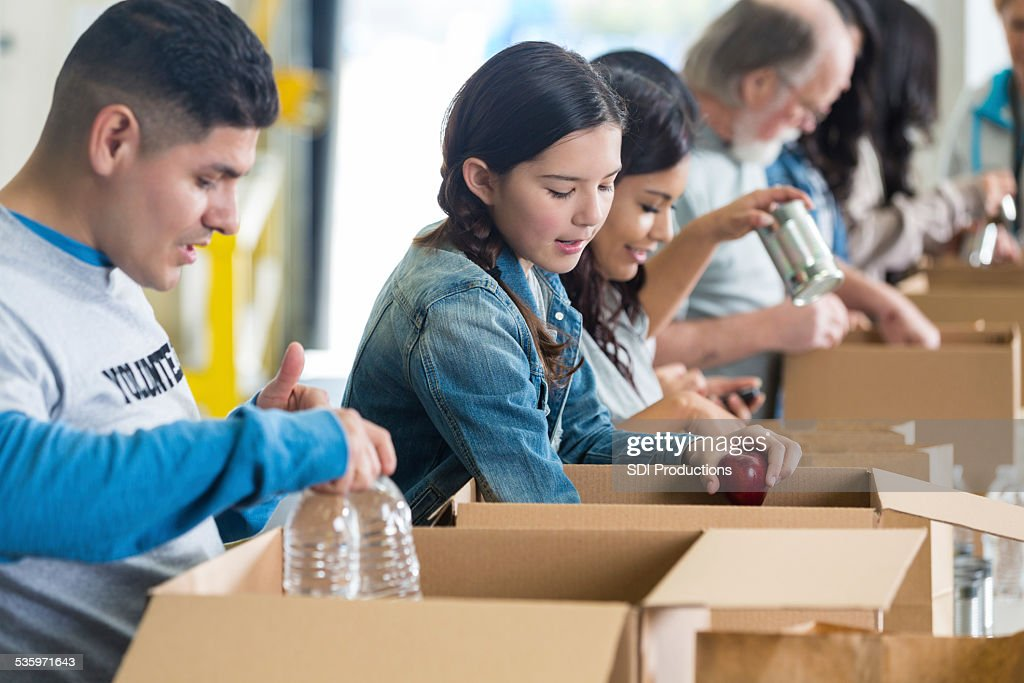 Diverse group of volunteers sorting food donations into boxes : Stock Photo