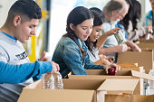 Diverse group of volunteers sorting food donations into boxes