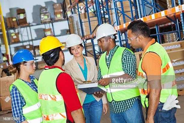 Grupo diverso de trabajadores de almacén revisando tarea de gerente