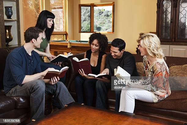 Groupe diversifié de jeunes adultes sur une Bible d'étude