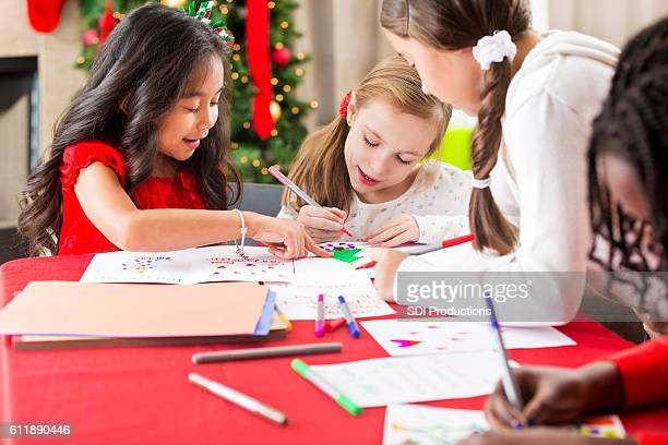Diverse group of young girls making Christmas cards