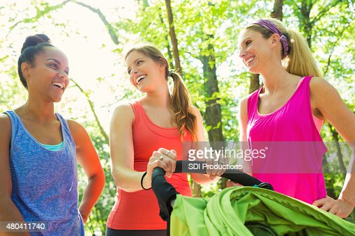 Diverse group of young moms exercising together in park