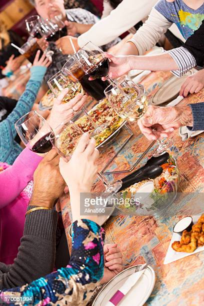 Diverse hands of people raising glasses together in restaurant