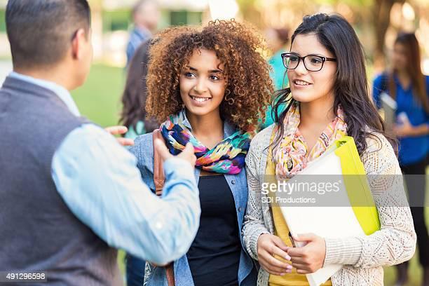 Diverse high school girls talking to professor outdoors after class