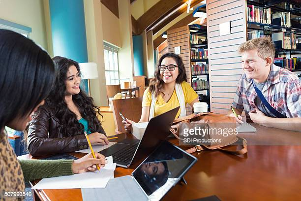 Diverse high school or college students studying together in library