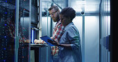 Modern multiethnic man and woman with tablet using laptop in server room while checking servers