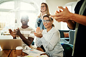 Positive group of diverse business colleagues clapping together during a meeting while sitting in a modern office