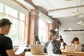 Diverse people focused on work in modern loft co-working space interior, businessman talking on phone while other businesspeople using laptops working with documents sitting at shared office desks