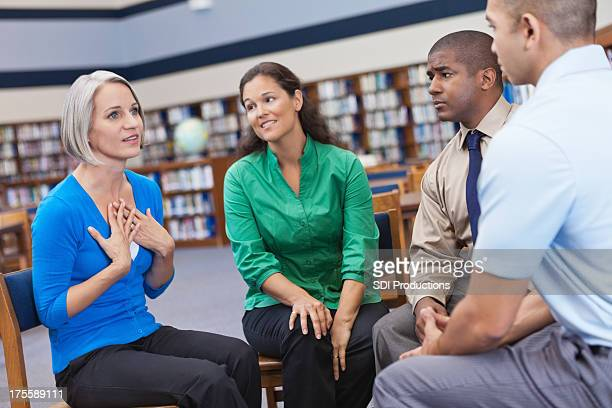 Diverse people having discussion in a group support meeting