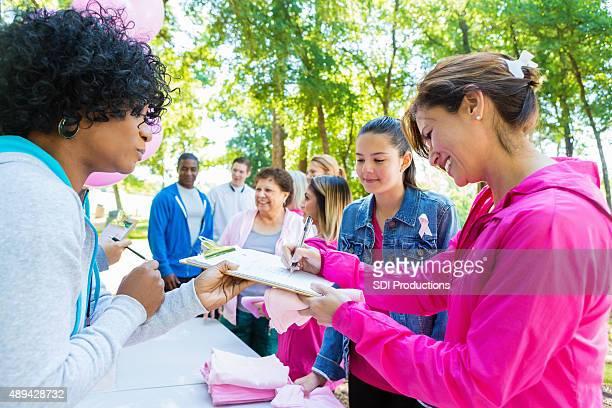 Verschiedene Menschen Ihre Registrierung für die charity Brustkrebs race