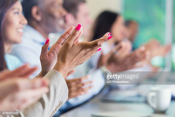 Diverse professional colleagues applauding speaker at business conference