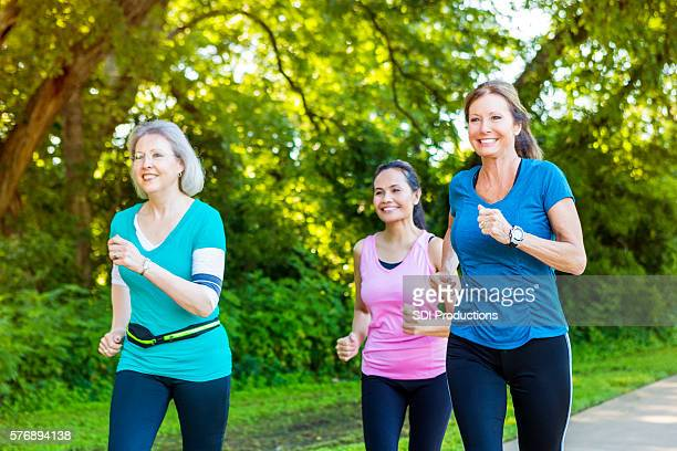 Diverse senior female friends jog on sunny day