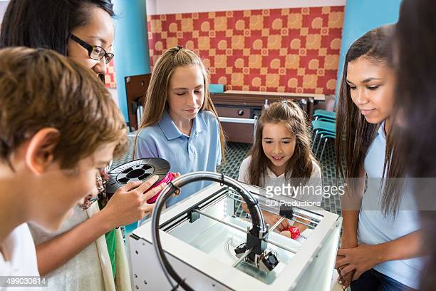 Diverse students watching 3D printer print object in class