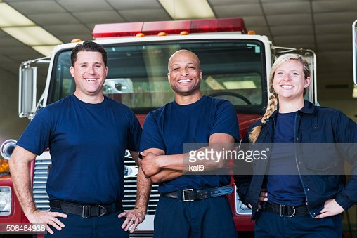Diverse team of firefighters in front of fire engine