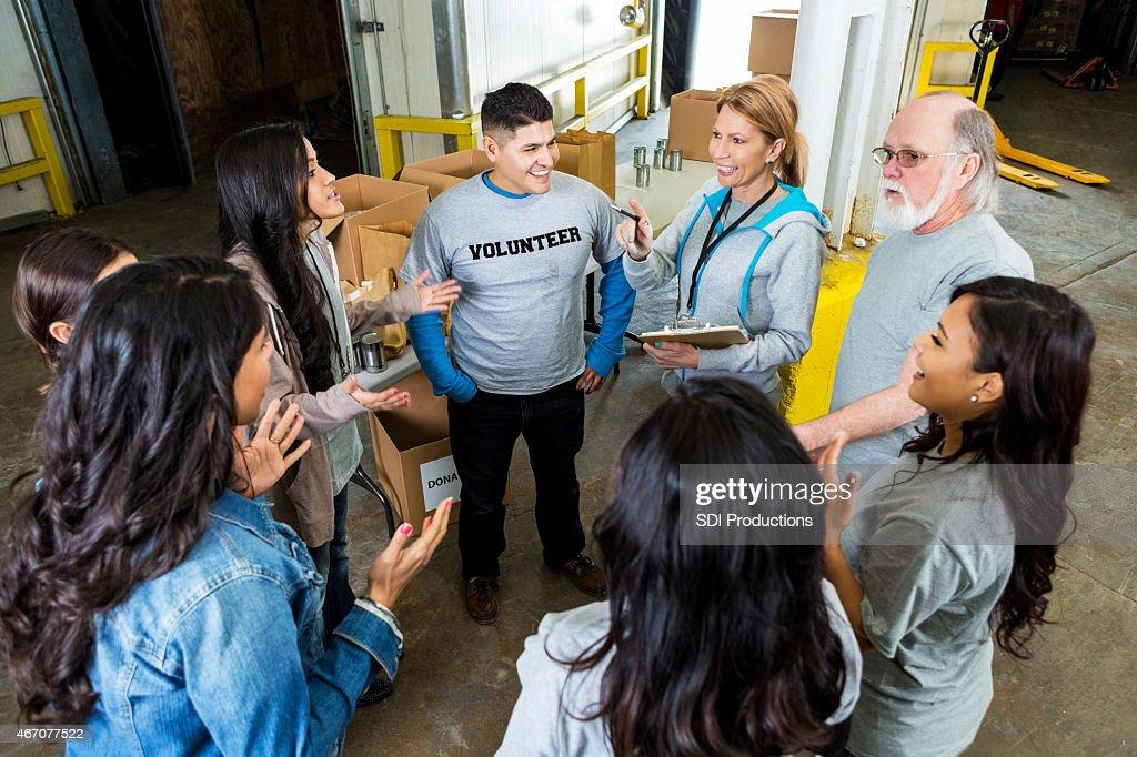 Diverse team of friends volunteering in community food bank