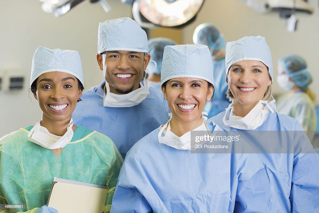 Diverse team of hospital surgeons in operating room : Stock Photo