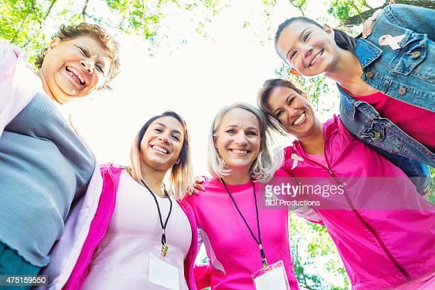 Diverso equipo de mujeres en la caridad carrera contra el cáncer de mama