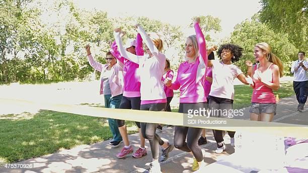 Diverse team of women winning marathon for breast cancer awareness