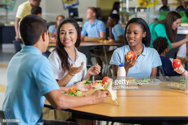 Diverse teenage friends eat lunch in school cafeteria