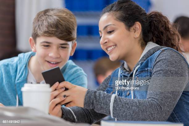 Diverse teenagers look at smart phone together