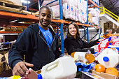 Diverse volunteers sorting boxes in assembly line at food bank