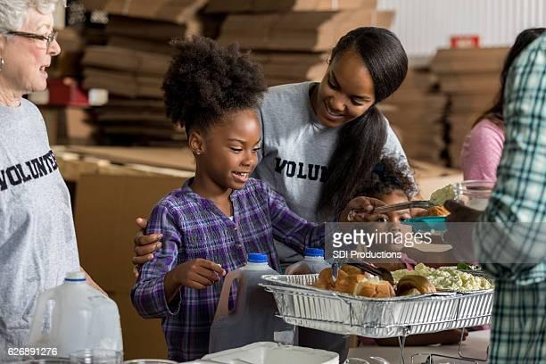 Diverse volunteers serve food in soup kitchen