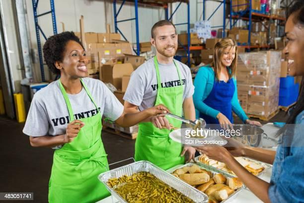 Diverse volunteers serving hot meal at soup kitchen