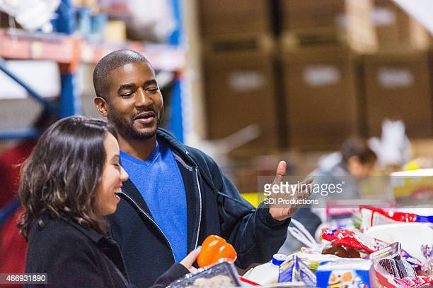 Diverse volunteers sorting donations in food bank assembly line