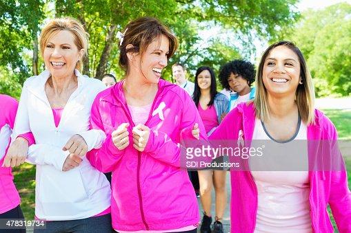 Diverse women walking in breast cancer awareness marathon race