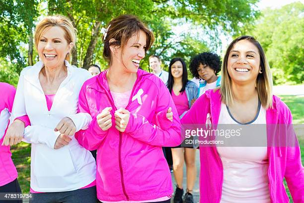 Diverse women walking in breast cancer awareness marathon race