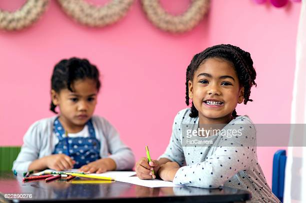 Diverse young African American sisters drawing pictures