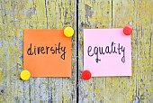 Stickers with words Diversity and Equality on wooden background