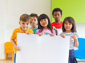 Diversity children holding blank poster in classroom at kindergarten preschool,Multiethnic Group with sign board,mock up for adding text or design.
